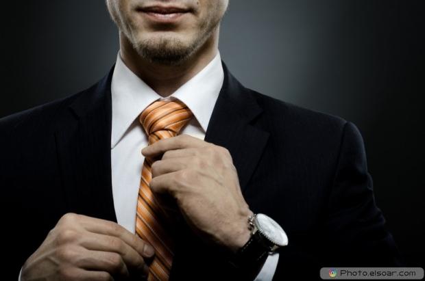 Beautiful businessman in black costume tie one's necktie
