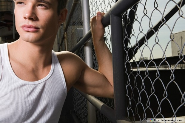 Close-Up. Young Man Leaning On A Fence