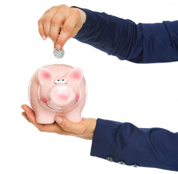 Closeup on business woman hands putting coin into piggy bank