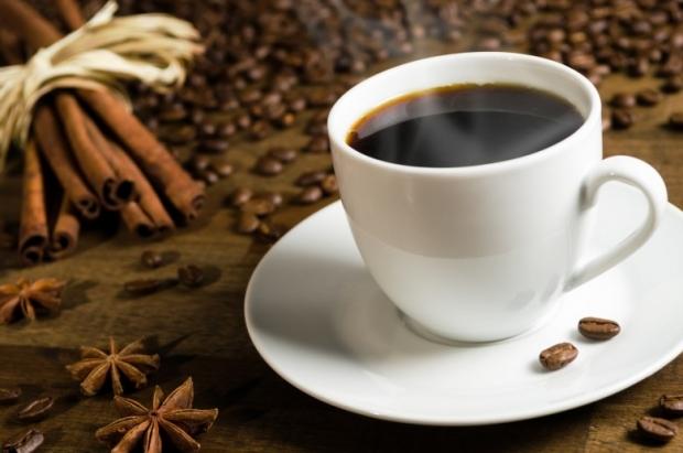 Coffee cup with coffee beans, cinnamon sticks