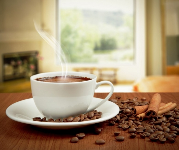 Cup of coffee with cinnamon, beans