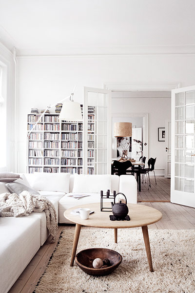 the living room with a coffee table and bookshelves in the background