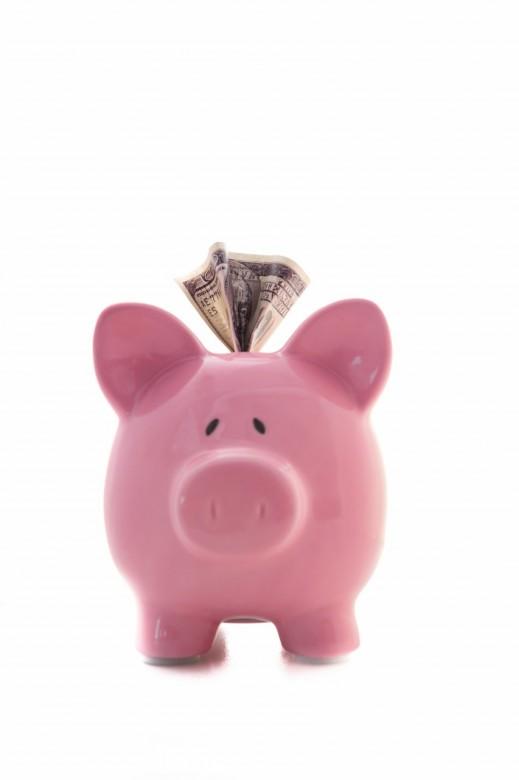 Dollar sticking out of pink piggy bank