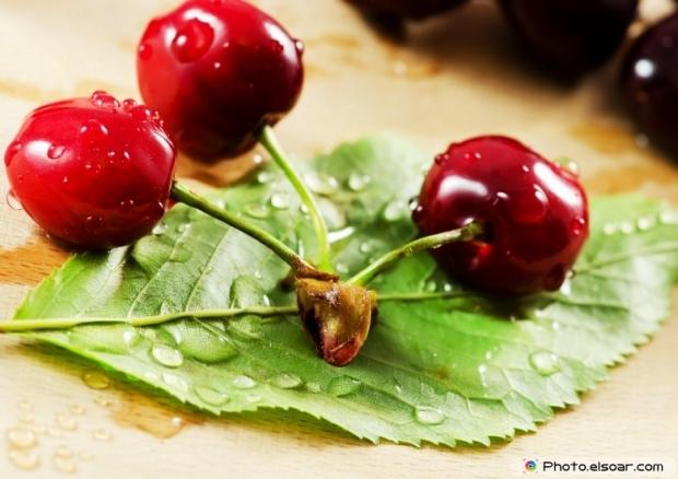 Fresh Cherries Over Green Leaf