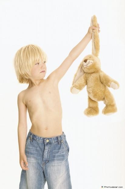 Funny Boy Looks At A Teddy Bear With Disdain