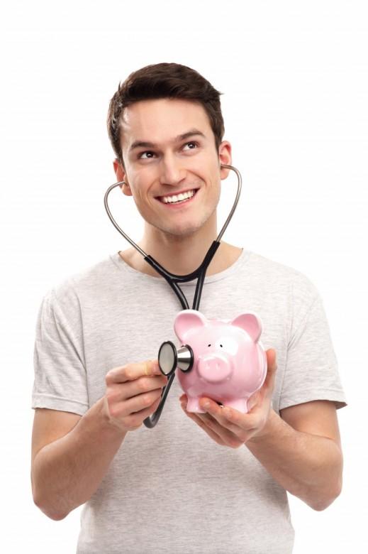 Man examining piggy bank with stethoscope