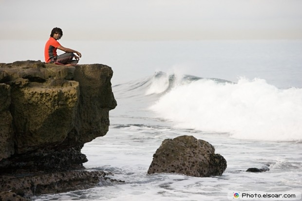 Man sitting on a rock by the sea