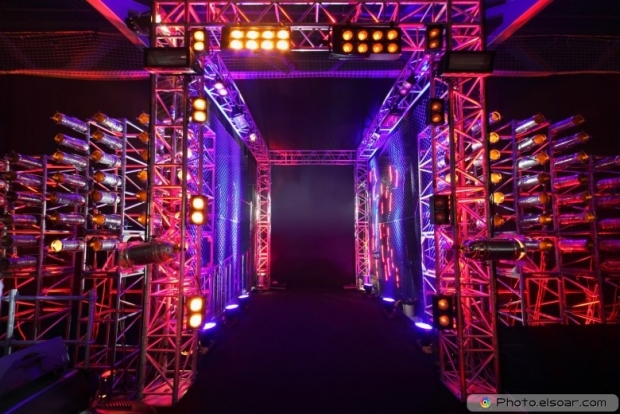 Multi-colored illuminated way with grid to boxing ring inside fight club