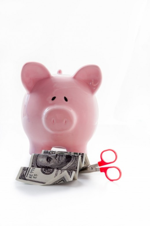 Scissor cutting dollar note in front of piggy bank