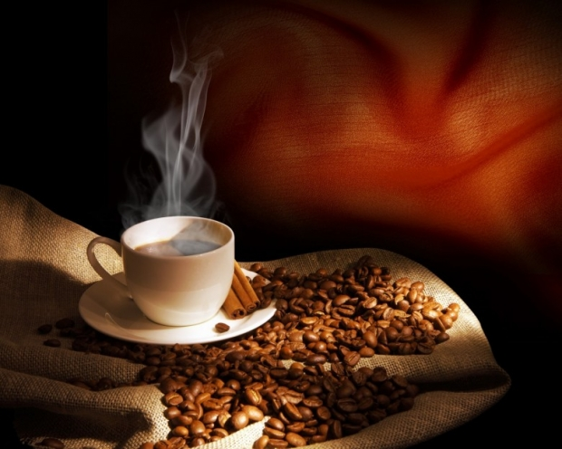 Steaming cup of coffee, cinnamon sticks, beans